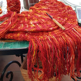 a bright red and orange knitted purse with a long fringe sits on a mosaic table top. on top of the purse rests a thin crochet hook with wooden handle