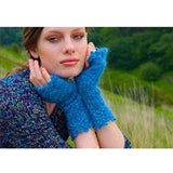 Swinstry fingerless lace mitts  from Louisa Harding's Winter's Muse Landscapes Pattern Book. a woman sits in tall grasses wearing cobalt blue knit fingerless gloves with lace trim