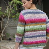 Woman standing showing the back of her sweater with is a knitted basketweave featuring a lace pattern in alternate squares. The yarn changes color to create horizontal stripes of pink, green, purple and grey, all in soft pastel shades. The colors an ¾ length sleeves give it a very feminine feel.
