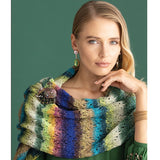 Blonde Woman with her hand on her chin wearing a colorful striped knitted lacey wrap around her shoulders. It's pinned in place with a jewel encrusted elephant pin. The wrap features stripes of greens yellows blues whites, its a veritable rainbow of colors