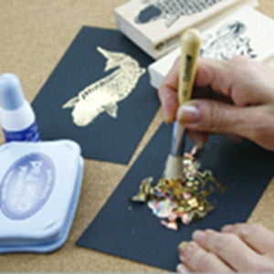 hands using a stipple brush to lay down gold foil on a black card
