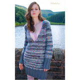 Whittledene Long V-neck sweater dress,  from Louisa Harding's Winter's Muse Landscapes Pattern Book. A woman stands in front of a lake wearing a blue grey and white striped knitted dress with a plunging v neck and over sized ribbing around her extra long sleeves and thighs