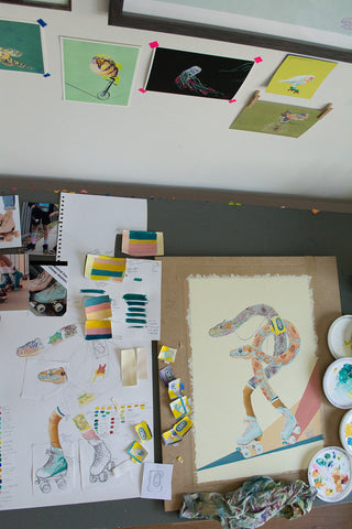 Painting of Western Australian Carpet Python snakes wearing Moxi roller skates on artist studio desk