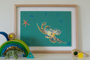 An artwork of a blue ringed octopus playing quoits with a starfish. The blue ringed octopus found off the coast of Western Australia. Painted with a predominately teal background. Artwork for boys teens bedroom. An artwork for marine life enthusiast. Gouache on paper, framed in sustainably managed Australian timber frame. Painted by artistic talent Jaelle Pedroli. Inspiration for kid's bedroom. Styled with dinosaur and wooden toys