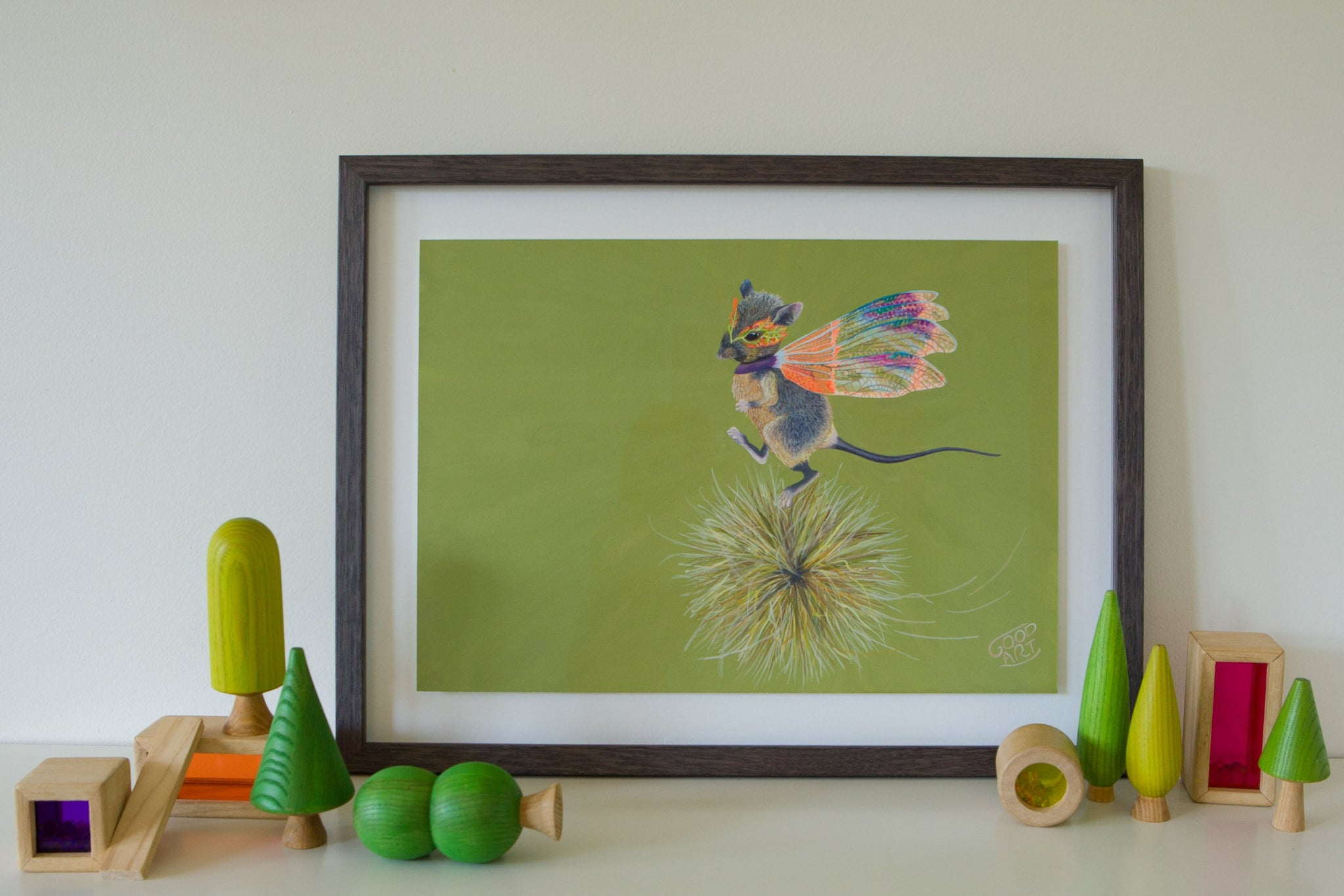 Western Australian marsupial, the Dunnart. Mouse-like in appearance. In this artwork the Dunnart wearing a set of dragonfly wings runs along on top of a spinning spinifix. A predominately olive coloured background. Artwork sits on shelf amongst wooden kids toys. Kids prints painted by artist Jaelle Pedroli.