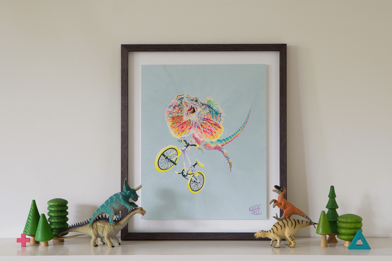 An art print for kids of an Australian frilled neck lizard riding a bmx bike flying over a jump. predominately light blue background. Framed original gouache painting sitting on shelf amongst timber toys and dinosaurs. An artwork for teen boy bedroom painted by artist Jaelle Pedroli.