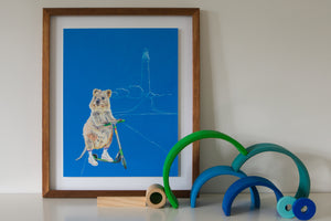 Artwork for a girls bedroom of Western Australian Rottnest Quokka riding a scooter with lighthouse in the background and a predominantly blue background. Framed original gouache painting, painted by Artist Jaelle Pedroli, sits on shelf in Australian themed bedroom.