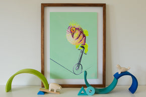 An artwork of a blowfish pufferfish fugu riding a unicycle on a tightrope. Circus themed art. Marine life art. Green background. Artwork for boys teens bedroom. An artwork for marine life enthusiast. Gouache on paper, framed in sustainably managed Australian timber frame. Painted by artistic talent Jaelle Pedroli. Inspiration for kid's bedroom. Styled with wooden toys.