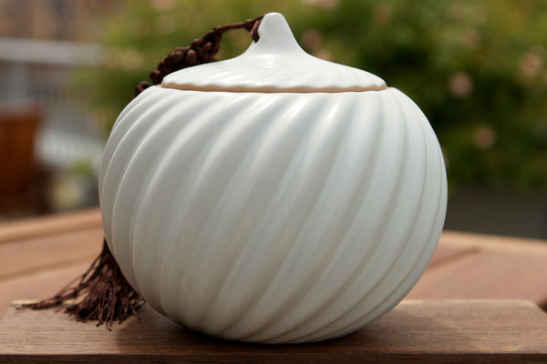 China white porcelain large tea container storage with ribbed walls design on the wooden table