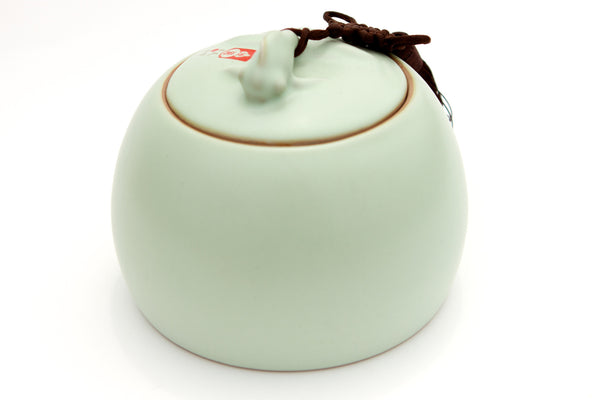 Tea storage container made of light green porcelain with fish on the lid