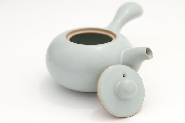 White plain porcelain teapot with long handle and open lid