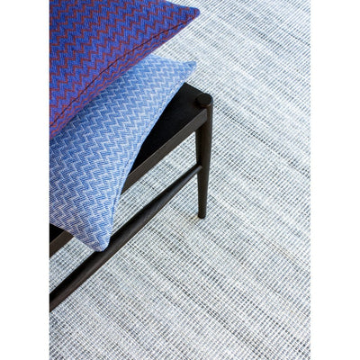 Ida Grey recycled plastic bottle rug by Claire Gaudion. Rug with chair and cushions.