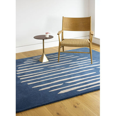 Island Blue Rug is an abstract lines patterned rug in two colours, blue and cream. The abstract lines pattern creates a circle shaped design within this rectangular wool rug. Pictured with chair and side table.