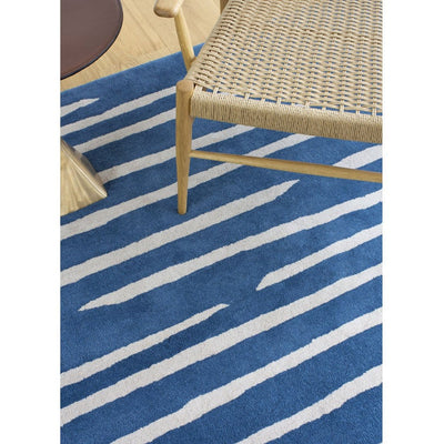Island Blue Rug is an abstract lines patterned rug in two colours, blue and cream. The abstract lines pattern creates a circle shaped design within this rectangular wool rug. Rug detail close up.
