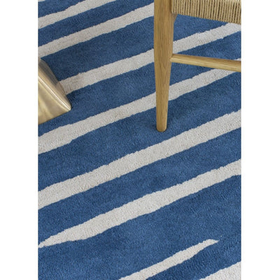 Island Blue Rug is an abstract lines patterned rug in two colours, blue and cream. The abstract lines pattern creates a circle shaped design within this rectangular wool rug. Rug close up.