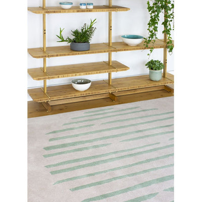 Island Leaf Rug is an abstract lines patterned rug in two colours, cream and green. The abstract lines pattern creates a circle design within this rectangular wool rug. Pictured with bookshelves.
