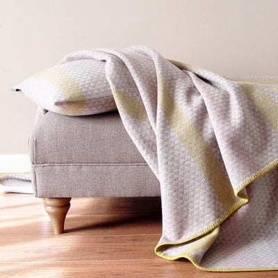 L'Ancresse Cushion is a natural colour cushion woven from 100% lambswool. This wool cushion is mostly natural cream and oatmeal coloured with gentle accent stripes in grey, pale pink and mustard yellow.  Pictured with matching throw on ottoman.