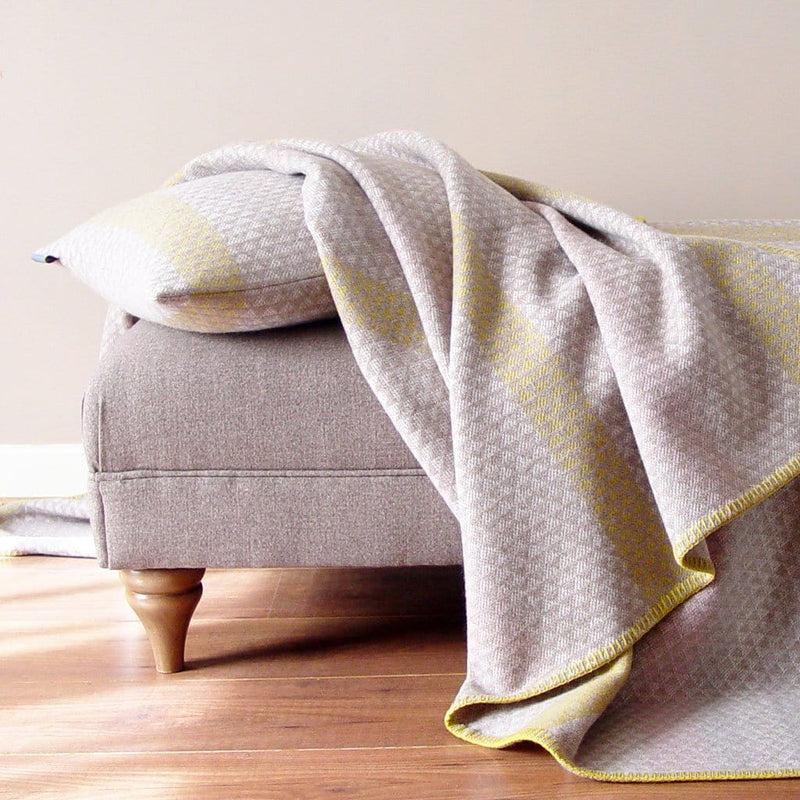 L'Ancresse Cushion is a natural colour cushion woven from 100% lambswool. This wool cushion is mostly natural cream and oatmeal coloured with gentle accent stripes in grey, pale pink and mustard yellow.