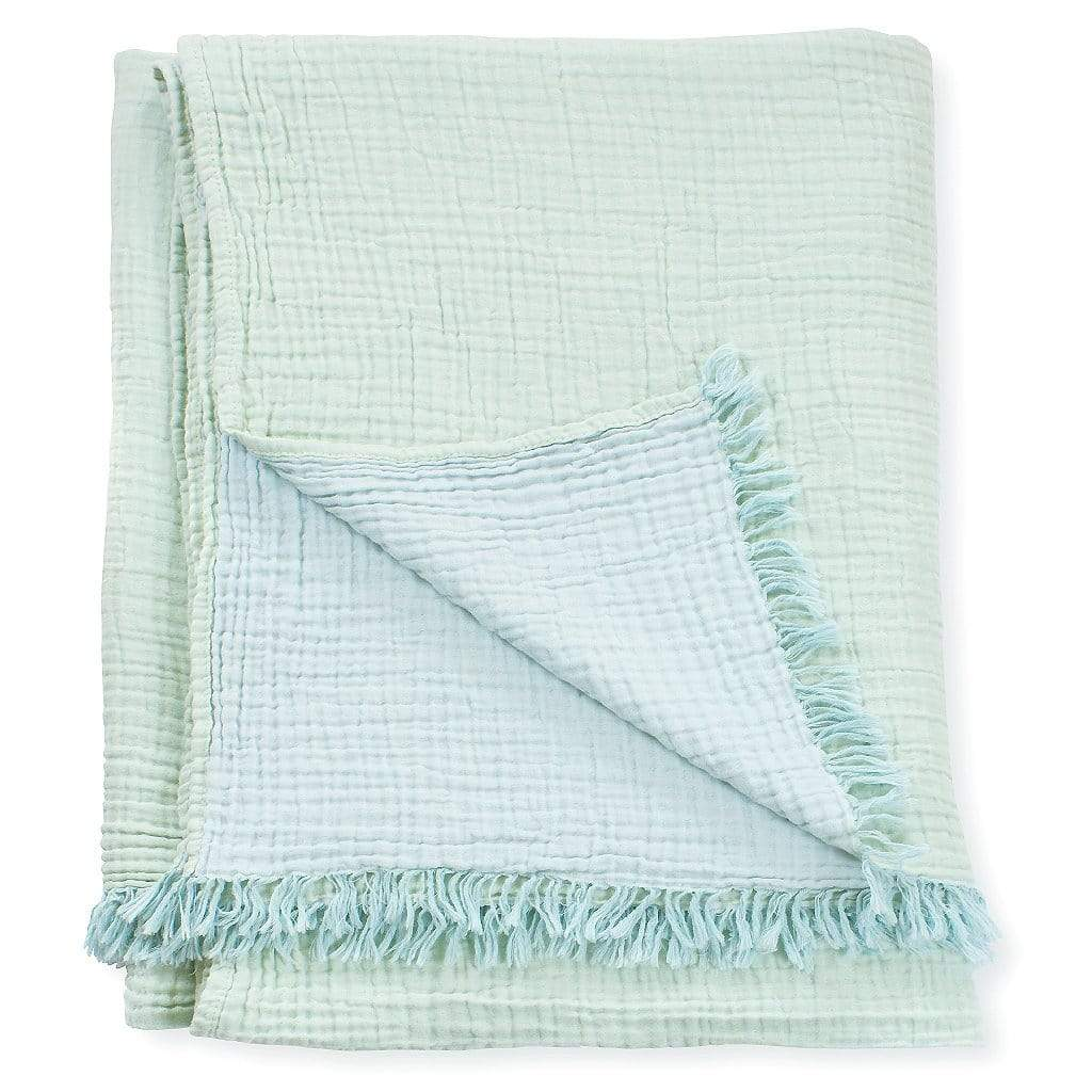 Lagoon Throw Blanket is a double-faced natural cotton throw in mint green and pale blue. The crinkled texture and tasselled ends give the throw a super-soft and inviting feel.  Photo shows the throw blanket folded.