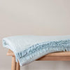Lagoon Throw Blanket is a double-faced natural cotton throw in mint green and pale blue. The crinkled texture and tasselled ends give the throw a super-soft and inviting feel. Photo shows the throw blanket folded on bench.