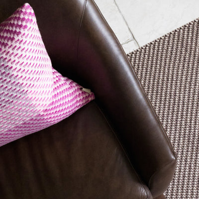Magenta Cushion is a decorative artisanal weave cushion, beautifully crafted in the UK. This woven cushion features the colours of a deep pink sunset with magenta, fuchsia and mid pinks interwoven with cream and grey neutrals. Cushion pictured on sofa.