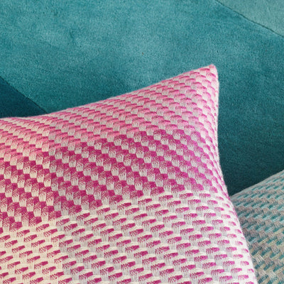 Magenta Cushion is a decorative artisanal weave cushion, beautifully crafted in the UK. This woven cushion features the colours of a deep pink sunset with magenta, fuchsia and mid pinks interwoven with cream and grey neutrals. Detail lifestyle photo.