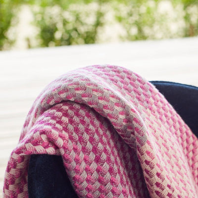 Magenta Throw is a luxury throw blanket that blends artisanal weave with beautiful craftsmanship. Mixed tones of pinks and neutrals create a beautiful textured weave effect. Pictured draped over chair. Close up photo.