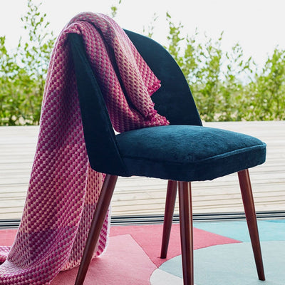 Magenta Throw is a luxury throw blanket that blends artisanal weave with beautiful craftsmanship. Mixed tones of pinks and neutrals create a beautiful textured weave effect.  The throw is draped over a chair and looks luxurious and soft.