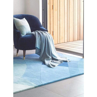 Rhythmic Tides Rug is a modern ocean themed rug that celebrates the sea. This coast rug is blue-green in colour and has an organic curved pattern which depicts the ebb and flow of the tides. Lifestyle image.