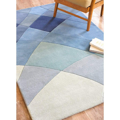 Rhythmic Tides Rug is a modern ocean themed rug that celebrates the sea. This coast rug is blue-green in colour and has an organic curved pattern which depicts the ebb and flow of the tides. Close up lifestyle image.