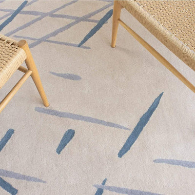 Sand Sketch Rug is a beautiful cream wool rug with a nature inspired, painterly pattern. Soft blue, grey and charcoal colours decorate the warm cream wool background.
