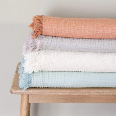 Shell Throw Blanket is a beautifully soft, pink and grey throw blanket with a crinkle-weave design and tasselled ends to give the throw a relaxed and characterful look. Throws pictured in a stack in different colours.