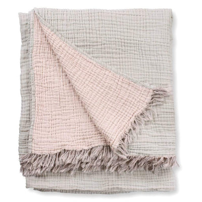 Shell Throw Blanket is a beautifully soft, pink and grey throw blanket with a crinkle-weave design and tasselled ends to give the throw a relaxed and characterful look.