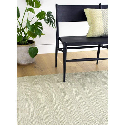 Tibba Fern Rug is a green recycled plastic bottle rug handwoven from 100% repurposed. The herringbone style weave is suited to modern and traditional homes. Rug styled with chair and plant.