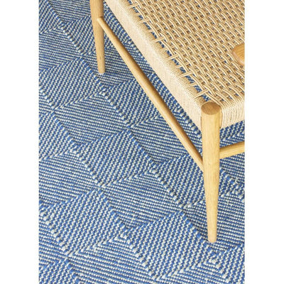 Zala Denim Rug - a blue recycled rug, handloom woven from 100% recycled plastic bottles. Our sustainable rugs are helping to combat plastic waste by using hundreds of recycled plastic bottles for each rug. Rug close up with wooden chair.