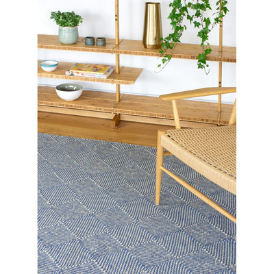 Zala Denim Rug - a blue recycled rug, handloom woven from 100% recycled plastic bottles. Our sustainable rugs are helping to combat plastic waste by using hundreds of recycled plastic bottles for each rug. Rug pictured with bookshelves and chair.