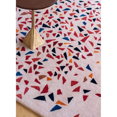 Lifestyle close-up image of Albecq Rug - a patterned modern rug with a colourful palette of reds, oranges and blues on a pink beige background.