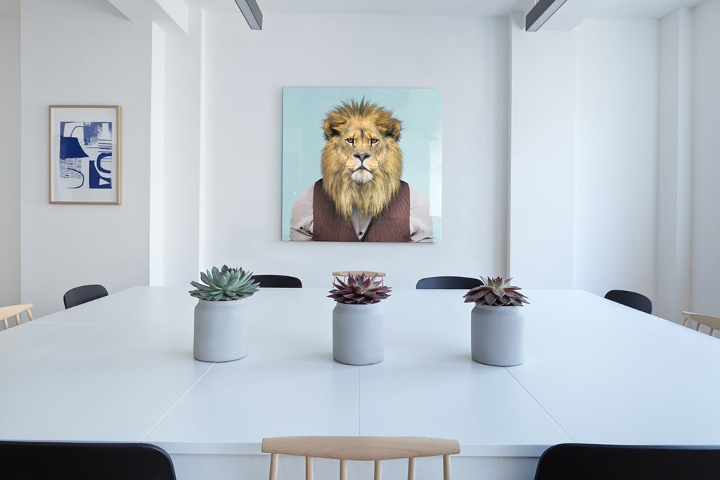 A lion dressed in a brown shirt and waistcoat in a conference room with a white table in the centre.