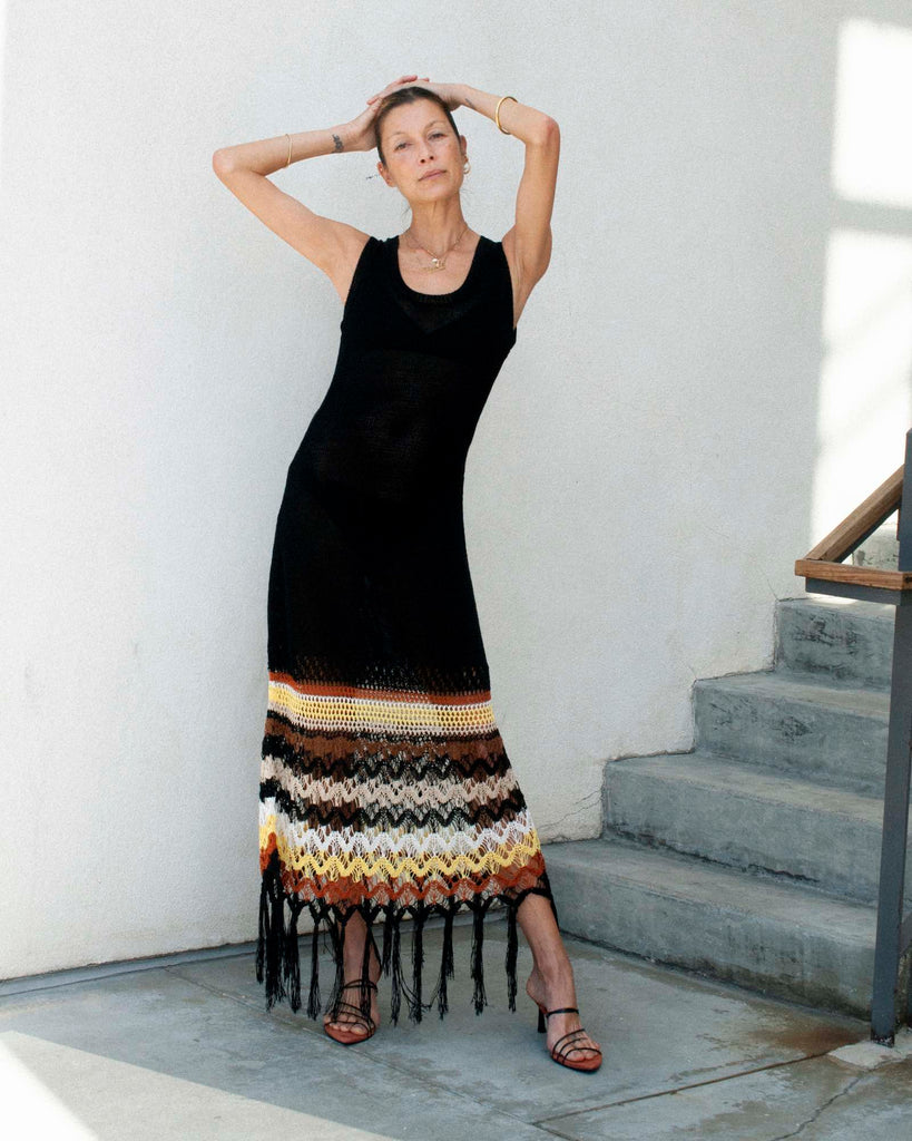Model stands against a white wall wearing a black knitted dress with her arms above her head.