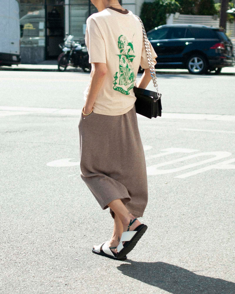Back view of model in the street wearing brown knit pants, white sandals, and a beige ringer t-shirt.