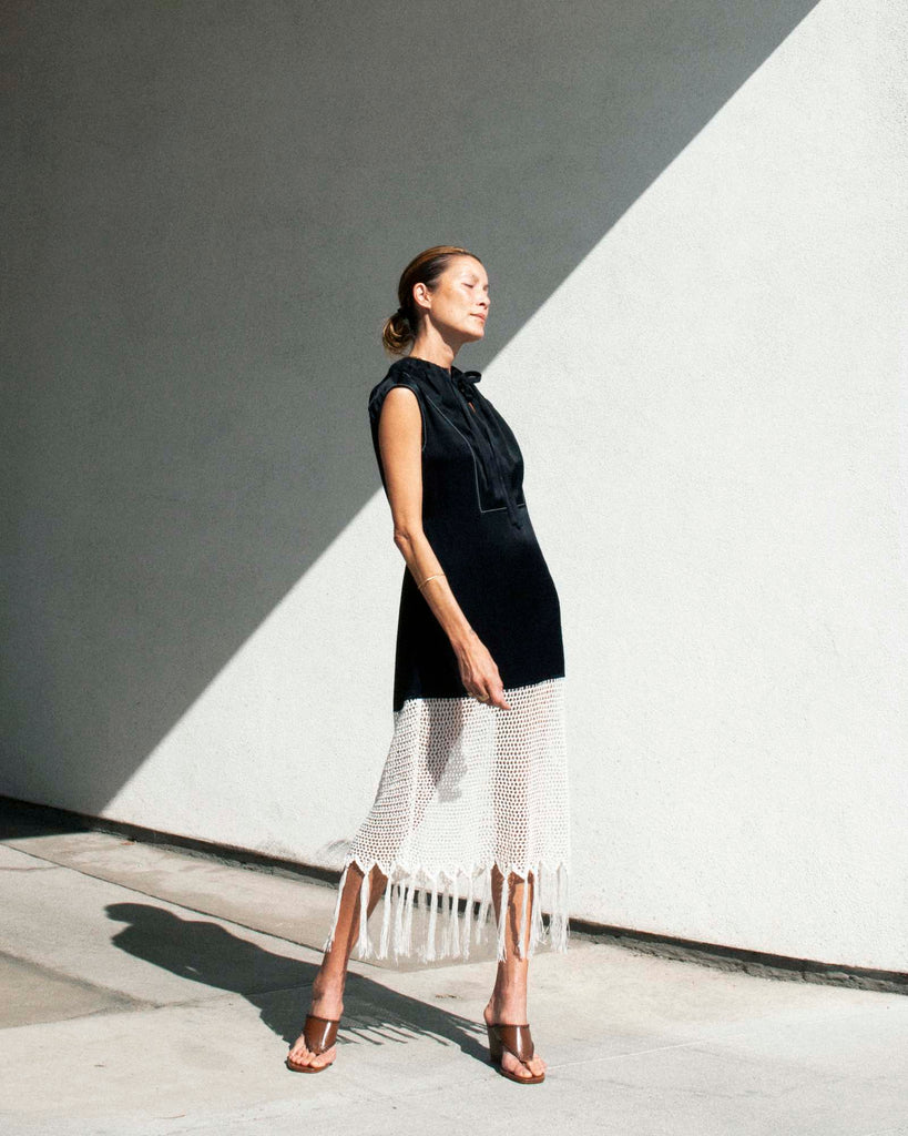 Model stands in the sun wearing a black and white crochet dress with brown thong sandals.