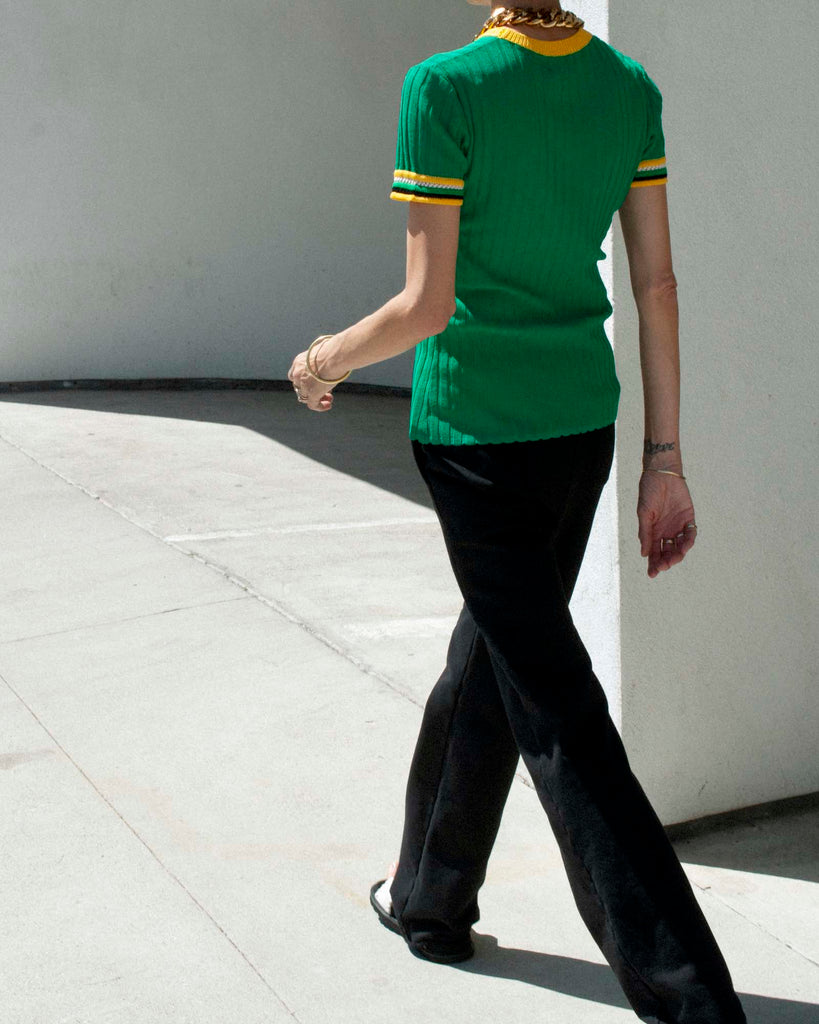 Back view of model walking wearing a green knitted t shirt and black tailored sweatpants.