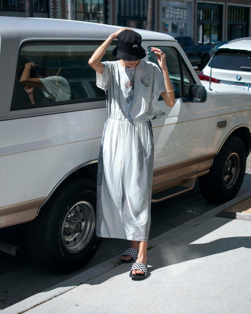 Model stands in front of a cream colored car, wearing a printed grey and white dress, black bucket hat, and checkered slide sandals.