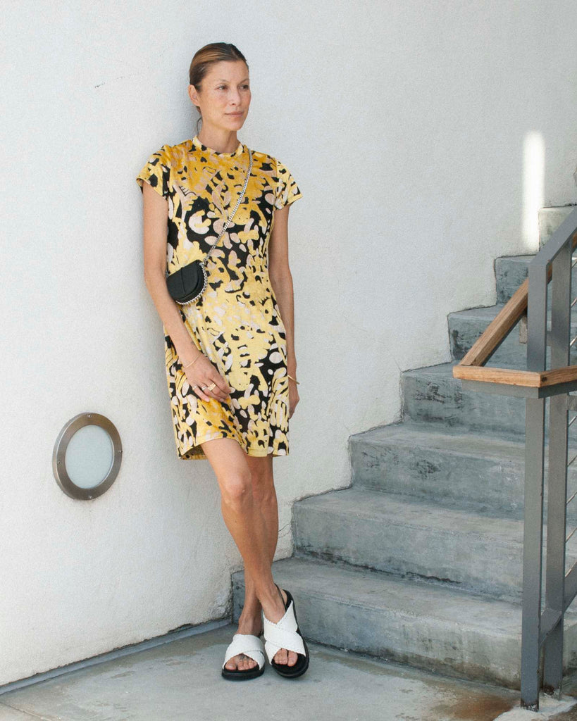 Model stands against white wall wearing a black and yellow printed mini dress and white sandals.
