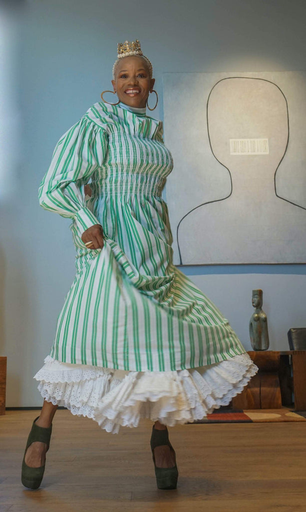 Starla stands indoors wearing a crown and green and white striped dress.