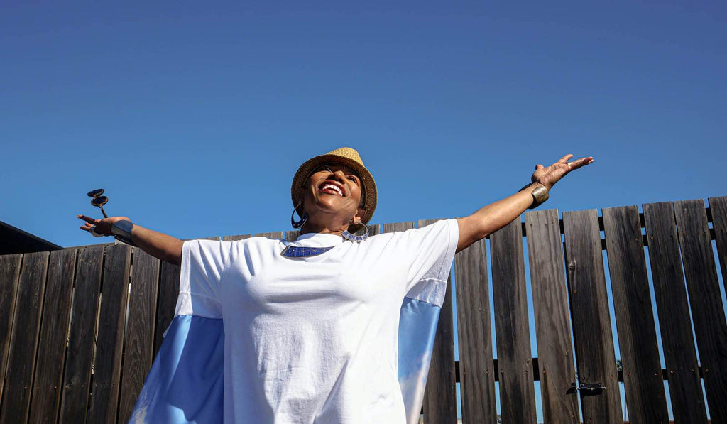 Starla stands outdoors with her arms wide, wearing a white t-shirt against the sky.