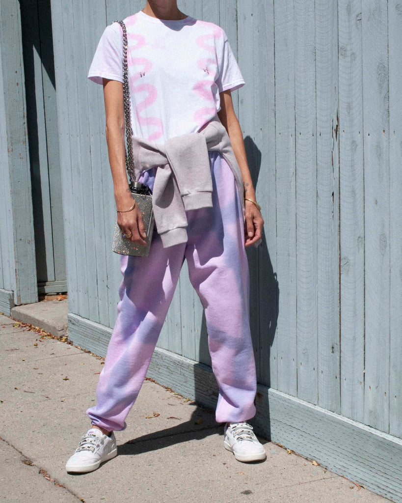 Model wears a pink and purple tie-dyed t-shirt and sweatpants on sidewalk in front of a blue wall.