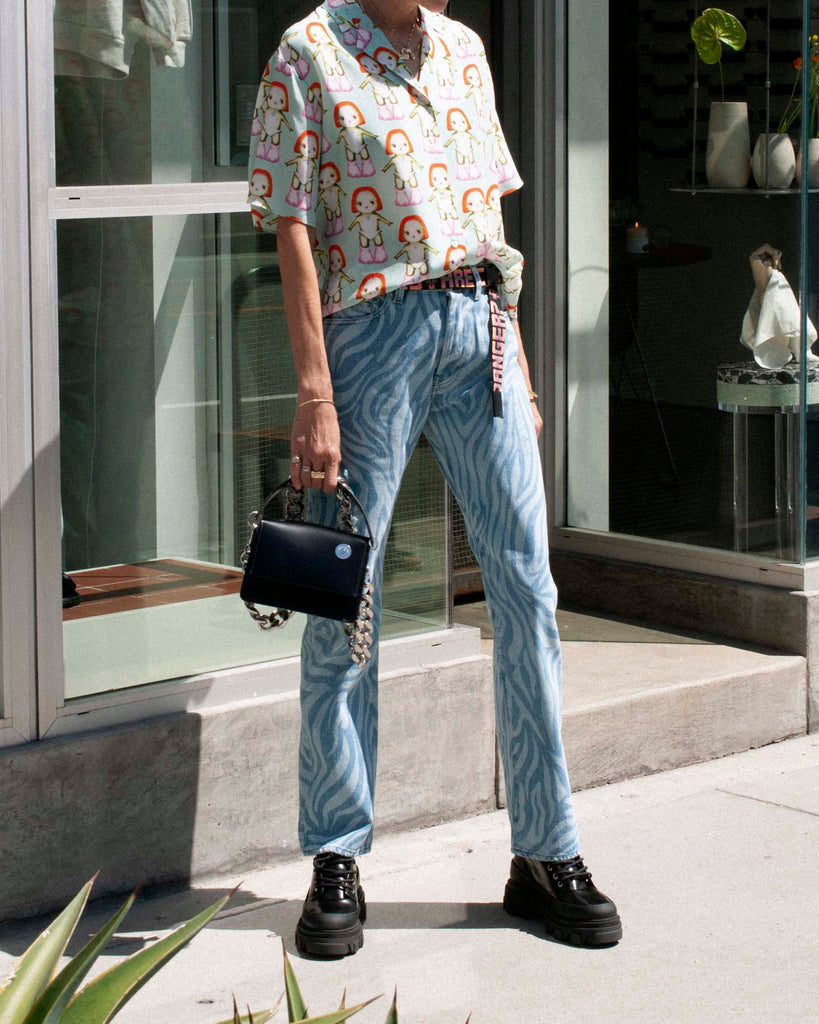 Model wears a printed short sleeve button up and zebra print jeans.