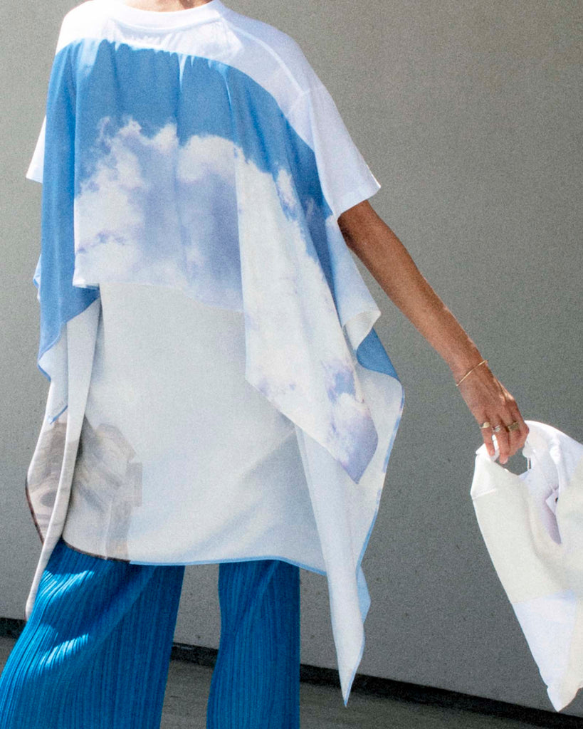 Back view of model wearing cloud print t-shirt and blue pants, holding white bag.