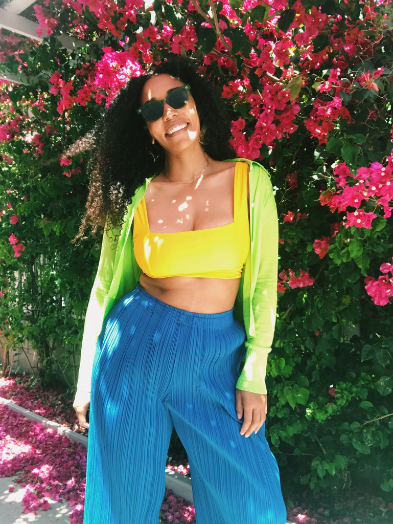 Model stands in front of bougainvillea, wearing a yellow sports bra, neon green cardigan, and electric blue pleated pants.
